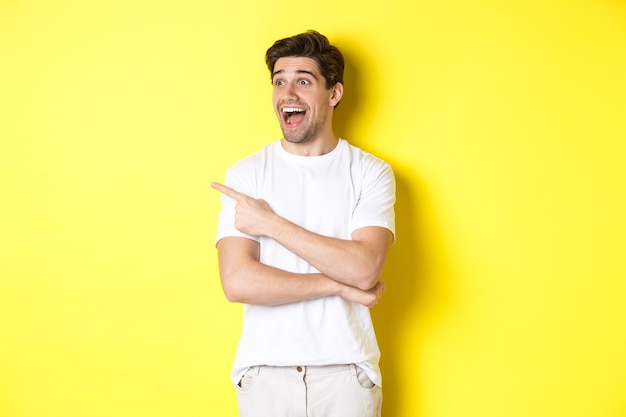Opgewonden glimlachende man wijst en kijkt naar links, promo-aanbieding uitchecken, staande op gele achtergrond.