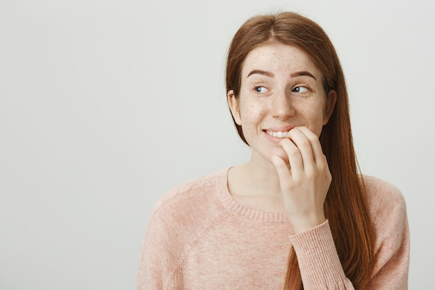 Opgewonden glimlachende roodharige vrouw raakt lip aan en kijkt links met verleiding