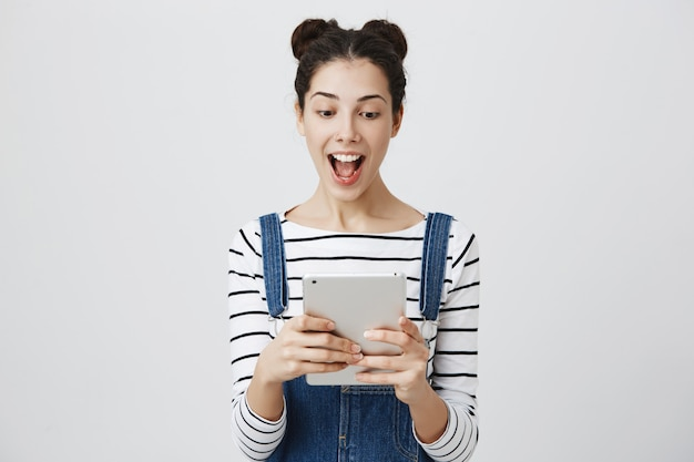 Opgewonden glimlachende vrouw die digitale tablet bekijkt
