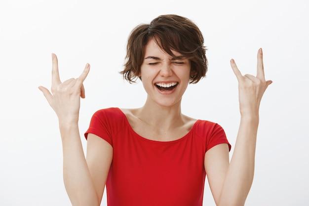 Opgewonden glimlachende vrouw die verbaasd kijkt en rock-n-roll-gebaar toont, plezier heeft