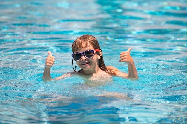 Opgewonden grappig kind met duimen omhoog in zonnebril in zwembad in zomerdag kind in zomerzwembad