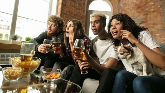 Opgewonden groep mensen die thuis naar het sportwedstrijdkampioenschap kijken