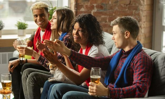 Opgewonden groep mensen die thuis naar sportwedstrijd kijken