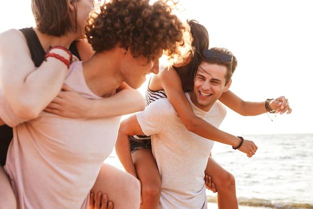 Opgewonden groep vrienden liefdevolle paren buiten wandelen op het strand met plezier