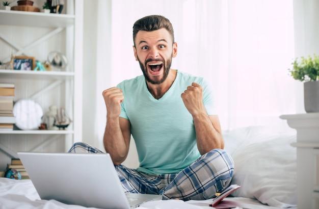 Opgewonden happy win fan bebaarde man met een laptop in een groot wit bed thuis schreeuwt terwijl de viering