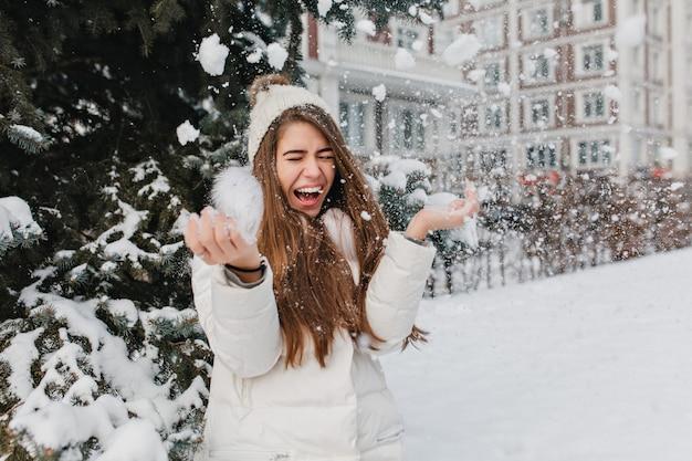 Opgewonden helder beeld van vrolijke verbazingwekkende mooie winter vrouw met plezier met sneeuw buiten op straat. gelukkige momenten, spelen met sneeuwvlokken, genieten, positieve emoties.