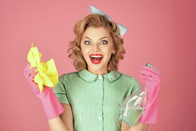 Opgewonden huishoudster vrouw in uniform met schone spray, spons. Premium Foto