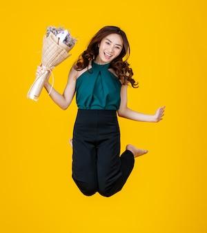 Opgewonden in liefde aziatische vrouwelijke brunette met een bloemboeket hoog springt vrolijk en erg blij de lucht in. stop actie bevriezen met studio-opname geïsoleerd op felgele achtergrond.