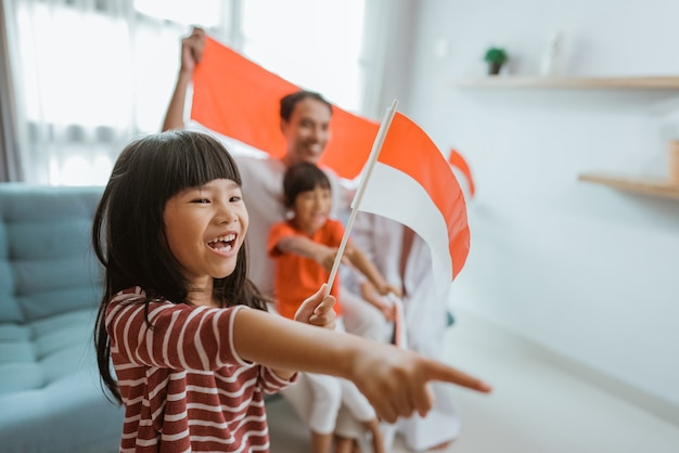 Opgewonden indonesische aanhanger van het kleine meisje tijdens het kijken naar sportwedstrijd op televisie thuis met familie op de achtergrond