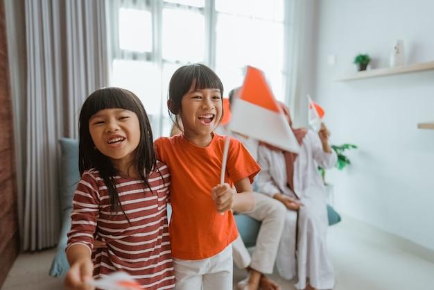 Opgewonden indonesische familiesupporter tijdens het kijken naar sportwedstrijd op televisie samen thuis