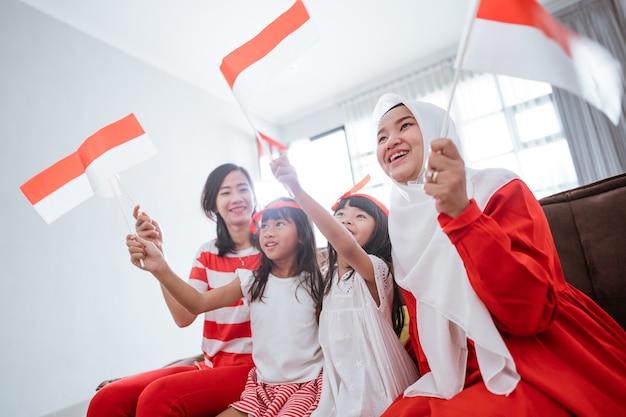 Opgewonden indonesische familiesupporter tijdens het kijken naar sportwedstrijd op televisie thuis