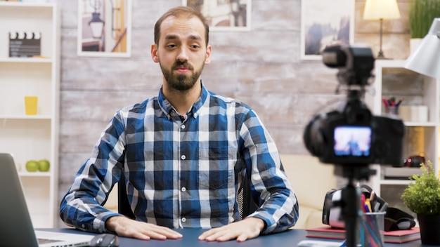 Opgewonden influencer tijdens het opnemen voor zijn vlog in de woonkamer. beroemde creatieve man.
