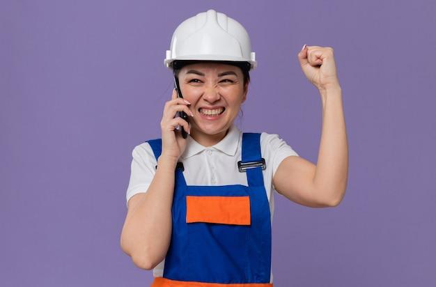 Opgewonden jong aziatisch bouwersmeisje met witte veiligheidshelm die aan de telefoon praat en de vuist omhoog houdt