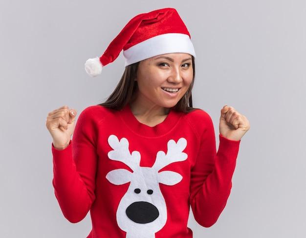 Opgewonden jong aziatisch meisje dat kerstmishoed met sweater draagt die ja gebaar toont dat op witte achtergrond wordt geïsoleerd