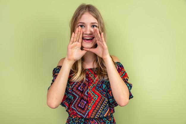 Opgewonden jong blond slavisch meisje houdt handen dicht bij haar mond en