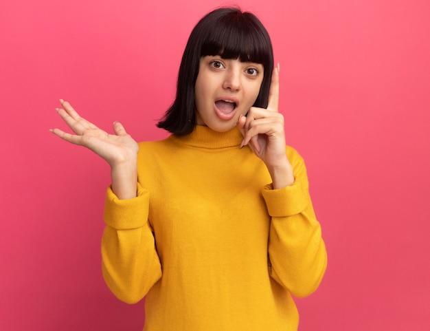 Opgewonden jong brunette kaukasisch meisje houdt hand open en wijst omhoog geïsoleerd op roze muur met kopieerruimte
