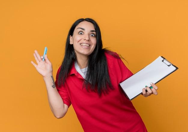 Opgewonden jong donkerbruin kaukasisch meisje dat rood overhemd draagt houdt pen en klembord dat op oranje muur wordt geïsoleerd
