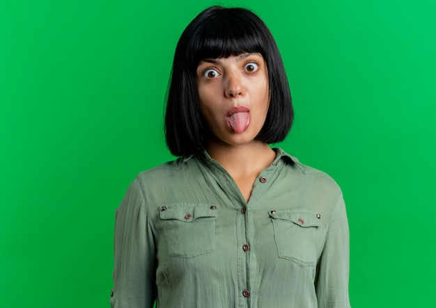 Opgewonden jong donkerbruin kaukasisch meisje stucks tong kijken camera geïsoleerd op groene achtergrond met kopie ruimte