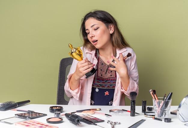 Opgewonden jong donkerbruin meisje dat aan tafel zit met make-uptools die make-upborstel vasthoudt en naar winnaarbeker kijkt