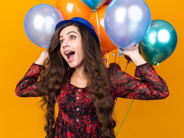 Opgewonden jong feestmeisje met een feesthoed die voor ballonnen staat en ze aanraakt terwijl ze naar de zijkant kijkt die op een oranje muur is geïsoleerd
