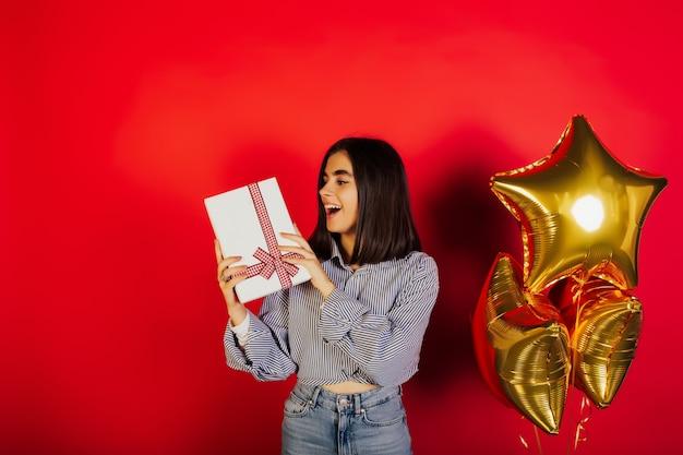 Opgewonden jong gelukkig meisje in blauw shirt en spijkerbroek houdt witte geschenkdoos met rode strik geïsoleerd op rood oppervlak.