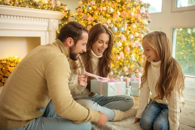 Opgewonden. jong gezin zittend op de vloer en kerstcadeaus uit te wisselen