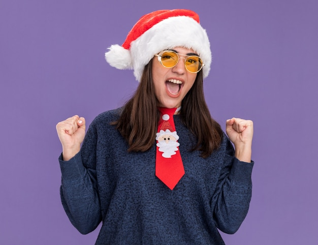 Opgewonden jong kaukasisch meisje in zonnebril met kerstmuts en kerststropdas houdt vuisten geïsoleerd op paarse muur met kopieerruimte