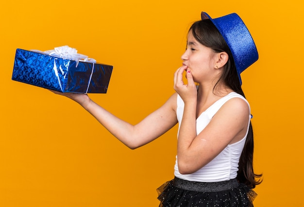 Opgewonden jong kaukasisch meisje met blauwe feestmuts die een geschenkdoos vasthoudt en kijkt die hand op de mond legt geïsoleerd op een oranje muur met kopieerruimte