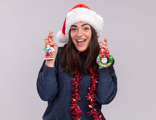 Opgewonden jong kaukasisch meisje met kerstmuts en slinger om nek houdt kerstboomspeelgoed