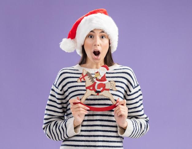Opgewonden jong kaukasisch meisje met kerstmuts met kerstman op schommelpaarddecoratie geïsoleerd op paarse muur met kopieerruimte