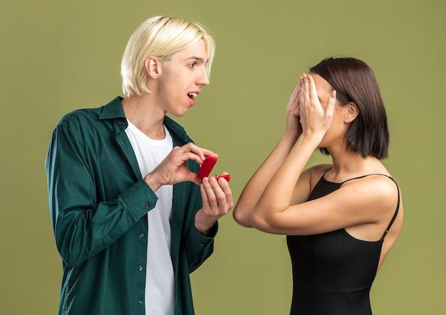 Opgewonden jong koppel op valentijnsdag man die verlovingsring geeft aan vrouw die naar haar kijkt en ze bedekt ogen met handen geïsoleerd op olijfgroene muur