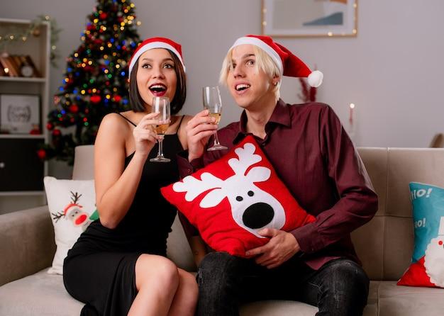 Opgewonden jong koppel thuis in de kersttijd met kerstmuts zittend op de bank in de woonkamer