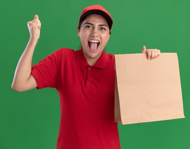 Opgewonden jong leveringsmeisje die eenvormig en glb dragen die document voedselpakket houden dat ja gebaar toont dat op groene muur wordt geïsoleerd