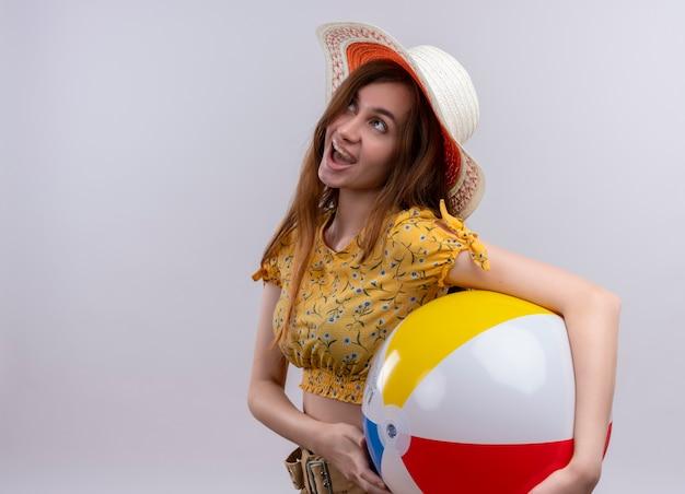 Opgewonden jong meisje dat het strandbal van de hoedholding draagt ?? die op geïsoleerde witte ruimte met exemplaarruimte omhoog kijkt