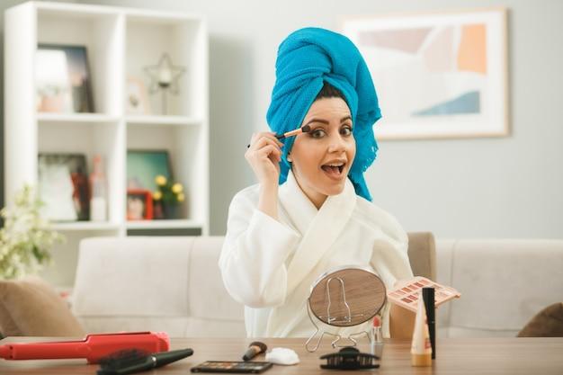 Opgewonden jong meisje dat oogschaduw aanbrengt met make-upborstel aan tafel met make-uptools in de woonkamer