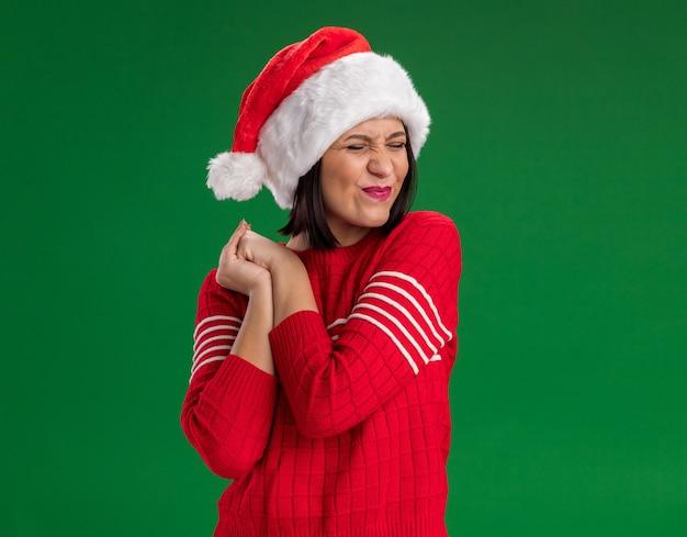 Opgewonden jong meisje dat santahoed draagt die handen samen met strak gesloten ogen houdt die op groene muur met exemplaarruimte worden geïsoleerd