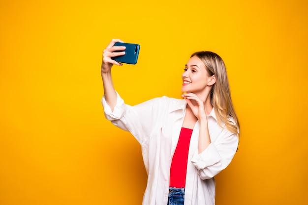 Opgewonden jong meisje dat vrijetijdskleding draagt die zich geïsoleerd over gele muur bevindt, selfie met uitgestrekte hand neemt