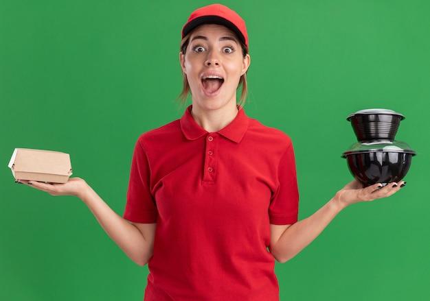 Opgewonden jong mooi bezorgmeisje in uniform houdt voedselcontainers en voedselpakket op groen