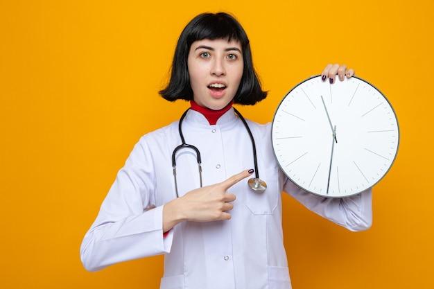 Opgewonden jong mooi kaukasisch meisje in doktersuniform met een stethoscoop die vasthoudt en op de klok wijst