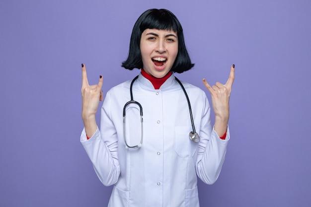 Opgewonden jong mooi kaukasisch meisje in doktersuniform met stethoscoop gebaren hoorns bord met twee handen