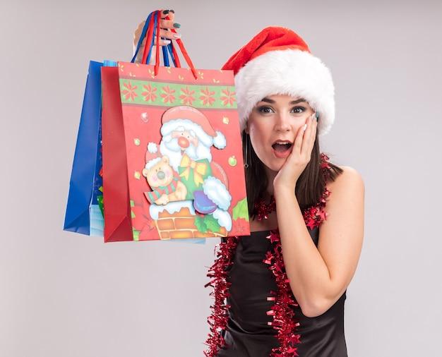 Opgewonden jong mooi kaukasisch meisje met kerstmuts en klatergoudslinger om de nek met kerstcadeautassen die hand op het gezicht kijken en kijken naar camera geïsoleerd op witte achtergrond