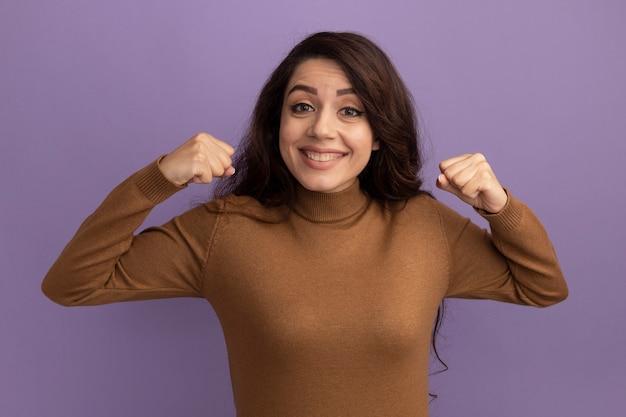 Opgewonden jong mooi meisje dat bruine coltrui draagt die ja gebaar toont dat op purpere muur wordt geïsoleerd
