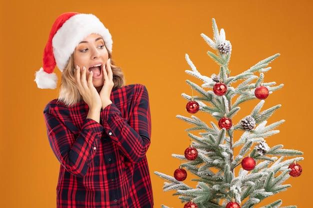 Opgewonden jong mooi meisje dat in de buurt van de kerstboom staat met een kerstmuts die handen op de wangen legt, geïsoleerd op een oranje achtergrond