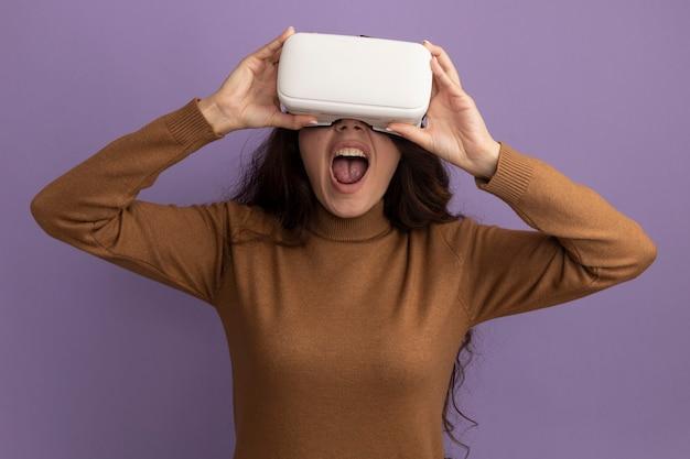 Opgewonden jong mooi meisje dat vr-headset draagt en vasthoudt, geïsoleerd op paarse muur