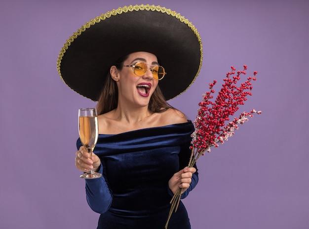 Opgewonden jong mooi meisje draagt blauwe jurk en bril met sombrero bedrijf rowan tak met glas champagne geïsoleerd op paarse achtergrond