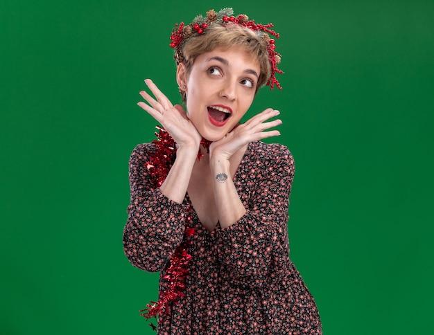 Opgewonden jong mooi meisje draagt ?? kerst hoofd krans en klatergoud slinger rond nek houden handen onder kin lookinh omhoog geïsoleerd op groene muur met kopie ruimte