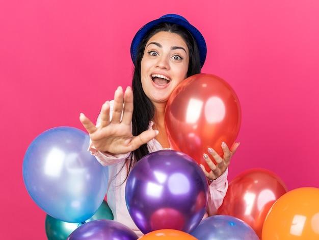 Opgewonden jong mooi meisje met feestmuts die achter ballonnen staat en hand uitsteekt die op roze muur is geïsoleerd