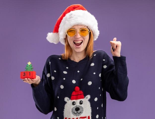 Opgewonden jong mooi meisje met kerst trui en hoed met bril met kerst speelgoed weergegeven: ja gebaar geïsoleerd op paarse achtergrond