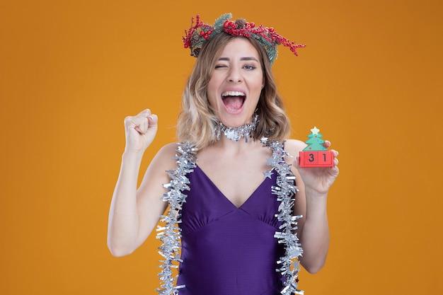 Opgewonden jong mooi meisje met paarse jurk en krans met slinger op nek met kerstspeelgoed met ja gebaar geïsoleerd op bruine achtergrond