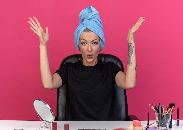 Opgewonden jong mooi meisje zit aan tafel met make-up tools gewikkeld haar in handdoek spreidende handen geïsoleerd op roze muur